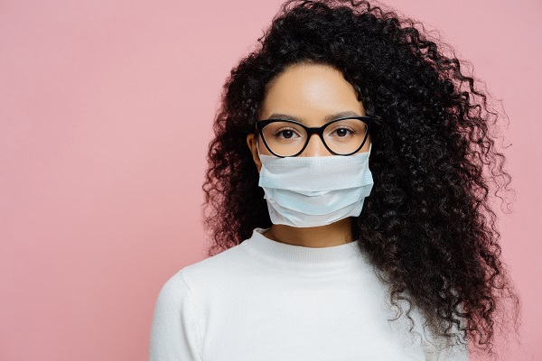 Covid-19, infectious virus. Close up shot of young woman with curly bushy hair, wears transparent glasses and medical disposable mask, cares about her health, protects in dangerious situation